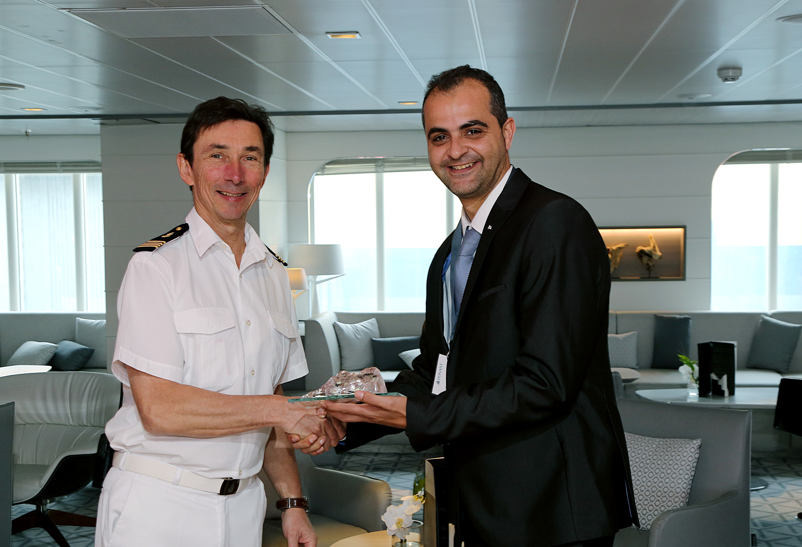 Ships Agency Manager Nico Bado, from Wilhelmsen, presents a gift to the Captain